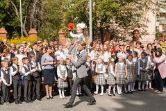 Girl ringing bell for first-graders - first bell. Tyumen, Russia - September 1, 2017: Gymnasium number 5. Older boy, teenager, caucasian, carries small Royalty Free Stock Image
