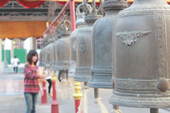 Girl ringing a row of temple bells at Wat Thai Stock Photo
