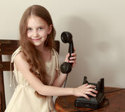 The girl rings on the old phone Royalty Free Stock Photography