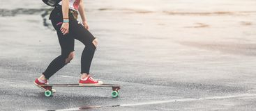 Girl with ripped jeans and red sneakers riding longbord Stock Images