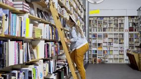 Girl rising on ladder and searching books. Side view of girl in hat rising on ladder choosing books on high top shelf in bookstore with decorative bicycle stock video footage