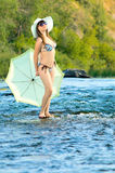Girl on river. Sexy slenderness beautifully girl standing on river, outdoor with  sunshade Royalty Free Stock Image