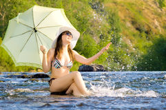 Girl on river. Sexy slenderness beautifully sit in river, outdoor with  sunshade, smile Stock Images