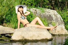Girl on river. Sexy slenderness beautifully sit on rock, outdoor with  bonnet, sun day Royalty Free Stock Image