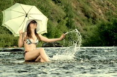 Girl on river. Sexy slenderness beautifully sit in river, outdoor with  sunshade, smile Stock Photo