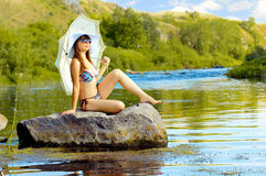 Girl on river. Sexy slenderness beautifully sit on rock, outdoor with  sunshade, smile Royalty Free Stock Photography