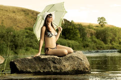 Girl on river. The sexy slenderness beautifully sit on rock, outdoor with  sunshade Royalty Free Stock Photos