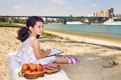 Girl by the river. Little girl with apples by the river Royalty Free Stock Image