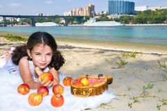 Girl on the river bank. Little girl with apples on the river bank Stock Photos