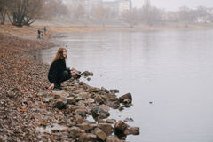 The girl on the river bank in the fall Stock Photography