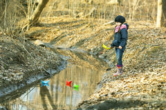 Girl on the river bank plays Paper Boat Royalty Free Stock Image