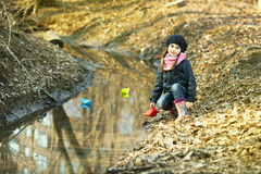 Girl on the river bank plays Paper Boat Stock Image