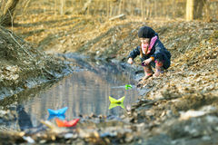 Girl on the river bank plays Paper Boat Royalty Free Stock Images