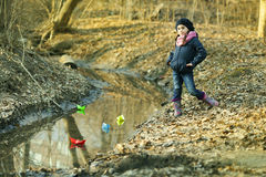Girl on the river bank plays Paper Boat Royalty Free Stock Photos