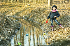 Girl on the river bank plays Paper Boat Stock Photography