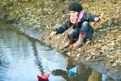 Girl on the river bank plays Paper Boat Stock Photo