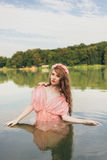 Girl in river. Girl in a dress in the water at dawn Royalty Free Stock Photo