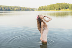 Girl in river. Girl in a dress in the water at dawn Stock Photography
