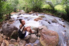 Girl by river in jungle stock photography