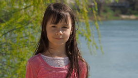 The girl by the river. Little girl near the water with developing hair. A spring sunny day. stock footage