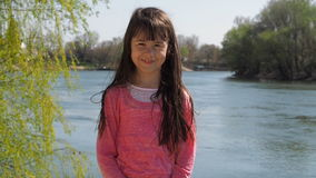 The girl by the river. Little girl near the water with developing hair. A spring sunny day. stock video footage