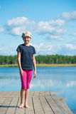 Girl on the river standing on the pier. A child stands on a pier in the background of the beautiful river Royalty Free Stock Image