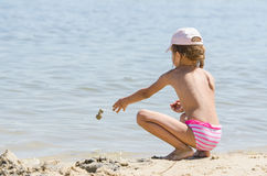 Girl on the river throws sand in water Stock Images
