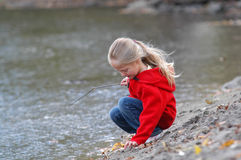 Girl On A Riverbank. A young girl plays on a riverbank near the water's edge Stock Photos