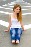The girl on the road. Girl standing beside the road on the dividing strip Stock Image