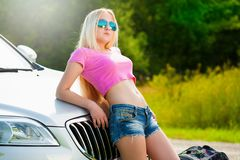 Girl in road car, pink t-shirt, blue shorts, half height Stock Photography