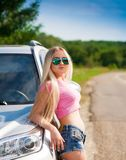 Girl in road car, pink t-shirt, blue shorts, half height, sexy Royalty Free Stock Photography