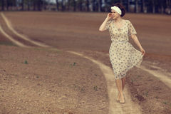 Girl on the road in  field Royalty Free Stock Image
