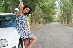 Girl on road greeting gesture near white car Stock Photo