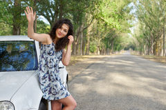 Girl on road greeting gesture near white car Royalty Free Stock Image