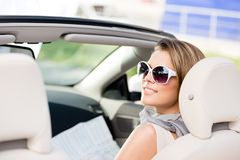 Girl with the road map in the car. Girl checks the way with the help of the highway map sitting in the car Royalty Free Stock Photo