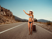 Girl on the road with a suitcase. Pretty young woman with suitcase hitchhiking along a road Royalty Free Stock Images