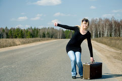 Girl on the road waiting for a car. Stay near vintage suitcase Stock Photography