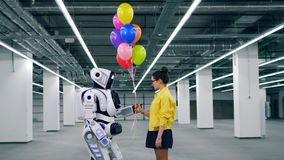 A girl and a robot are holding balloons together stock footage