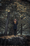 Girl on the rock. Girl stays on the rock with bunch of leaves in her hands Stock Image