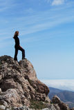 Girl on a rock. Girl standing at the edge of rock stock photography