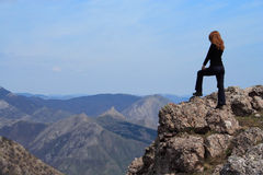 Girl on a rock. Girl standing at the edge of rock stock photos