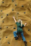 Girl Rock Climber. Young girl reaches new heights by aiming high Stock Photos