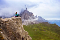 Girl on a rock. Girl hiker sitting at the edge of rock. Dolomites, Italy royalty free stock image