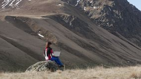 Girl on a rock with a laptop stock footage