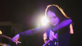 Girl rock musician - female drummer performing. Telephoto stock photography