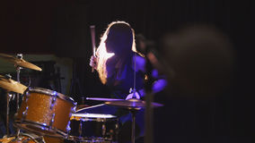 Girl rock musician - female drummer performing. Telephoto royalty free stock images