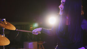 Girl rock musician - female drummer performing. Telephoto stock image