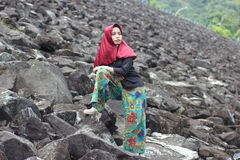 The girl on rock. She pretend to be a model. She stand and pose on the rock of bili-bili dam, gowa regency, south sulawesi, indonesia stock images
