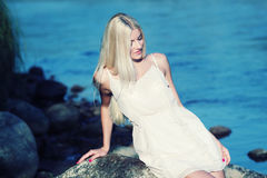 Girl on the rock. Romantic beautiful sweet girl sitting on a rock by the sea and enjoy Royalty Free Stock Image
