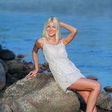 Girl on the rock. Romantic beautiful sweet girl sitting on a rock by the sea and enjoy Royalty Free Stock Photos